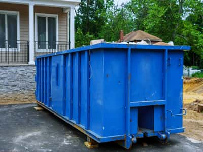 This is a picture of a 10 yard dumpster rental. The dumpster rental is on a construction site and the home is almost finished being built. This picture was taken in Fort Lauderdale, Florida.
