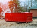 This is a picture of a red roll off dumpster rental on top of a construction site. Debris from the construction project will be disposed into this dumpster rental. This construction dumpster rental picture was taken in Fort Lauderdale, Florida.